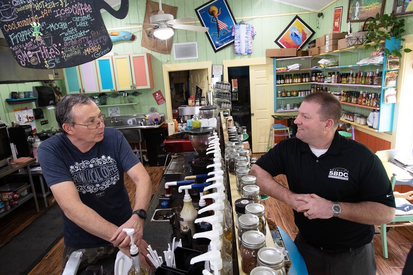 L-R: David Kiser, owner of Caribbean Coffee, shares with Michael Myhre, CEO of the Florida SBDC Network, how he storm impacted his cafe and about the progress he's made since the storm rolled ashore
