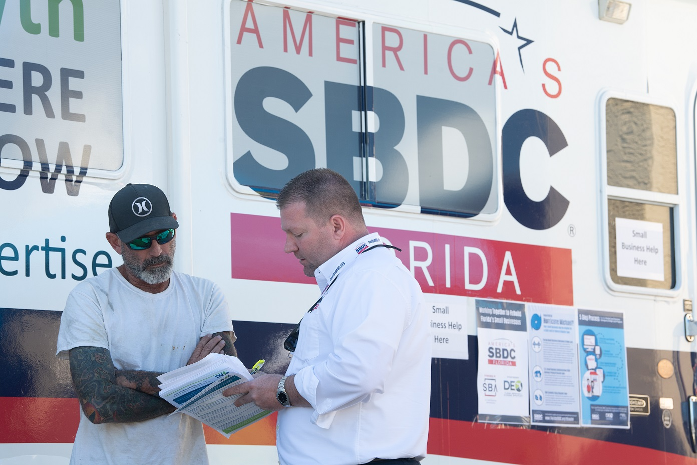 At the emergency response Mobile Assistance Center (MAC) Michael W. Myhre, CEO Florida SBDC Network, speaks with small business owner Robert Walker about getting help after Hurricane Michael hit Panama City, Florida.(Michael Spooneybarger/ Division of Research and Strategic Innovation)