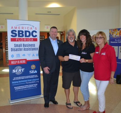 Mike Myhre, CEO of the Florida SBDC Network, presents the Viola's with a check for their Florida Small Business Emergency Bridge Loan following Hurricane Irma