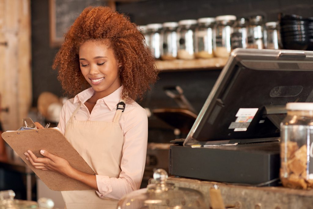 minority-owned business woman behind counter holding clipboard